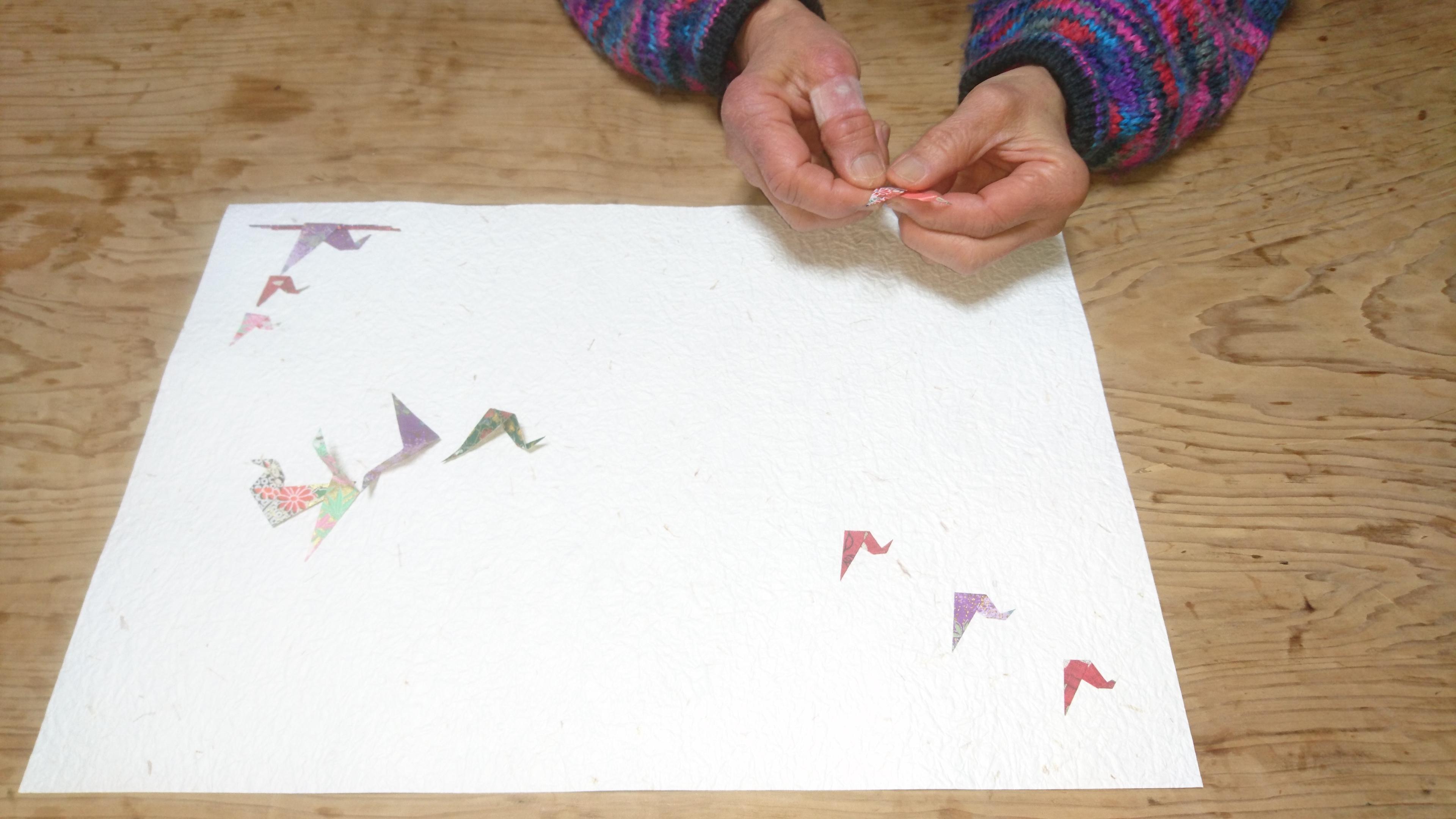 心を込めて折り鶴を作っています